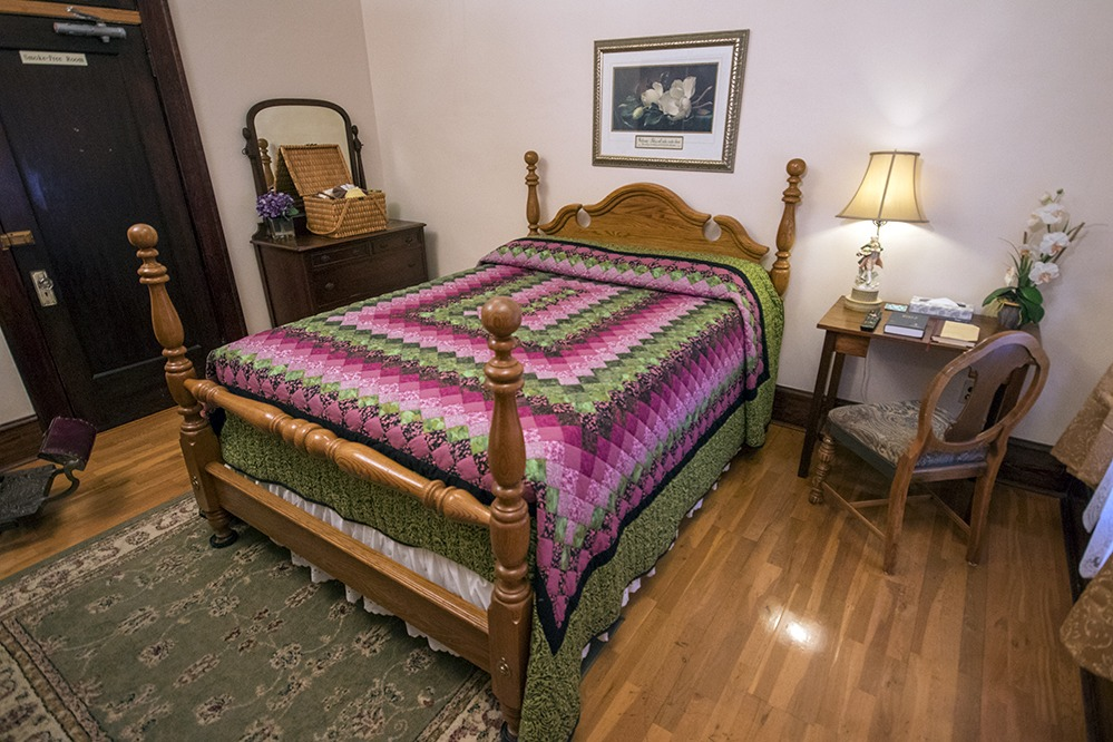 Hotel bed with pink quilt